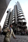 A city worker walks past the Lloyds of London building in London's financial district on March 24 2010 in London England In Parliament the Alistair...