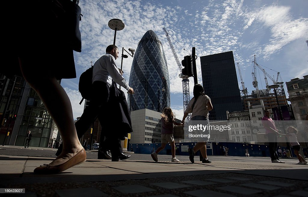 A city worker walks with pedestrians as he passes the Swiss Re Insurance building, also known as 'the Gherkin,' and construction cranes in London, U.K., on Friday, Aug. 17, 2012. Banks, insurers and other financial-services firms may eliminate a total of about 3,000 jobs across greater London as companies in the New York region add 9,000, according to U.K.-based researcher Oxford Economics Ltd. Photographer: Simon Dawson/Bloomberg via Getty Images