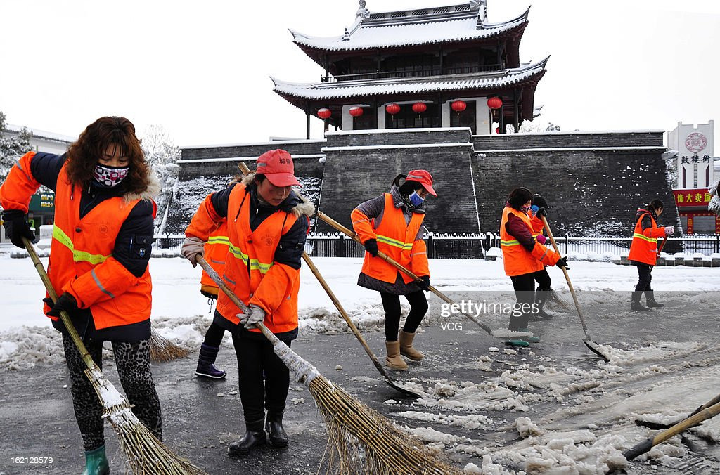 City workers clean a snow-covered road on February 19, 2013 in Yizheng, China. Heavy snow hit large areas of east China on Tuesday.