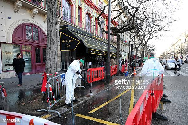 City workers clean the sidewalk and the street in front of the Bataclan concert hall in Paris on December 22 after the sidewalk in front of the venue...