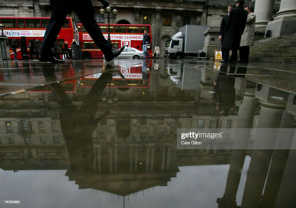 City workers pass the Bank of England in the rain on December 6, 2007 in London. The Bank of England has lowered its rates from 5.75 percent to 5.5 as a result of signs that the economy is slowing.