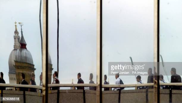 City workers reflected in a building as they cross London Bridge on foot as a 24 hour strike by thousands of workers on London Underground brought...
