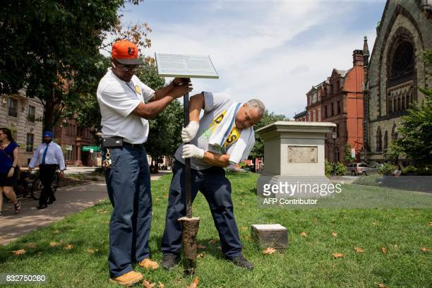City workers remove the detail sign at the former Roger B Taney monument in Mount Vernon Place in Baltimore Maryland after it was removed by the city...