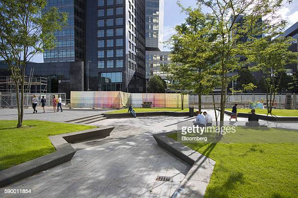 City workers sit in a green outdoor space between office buildings in the Zuidas business district of Amsterdam Netherlands on Monday Aug 15 2016 The...