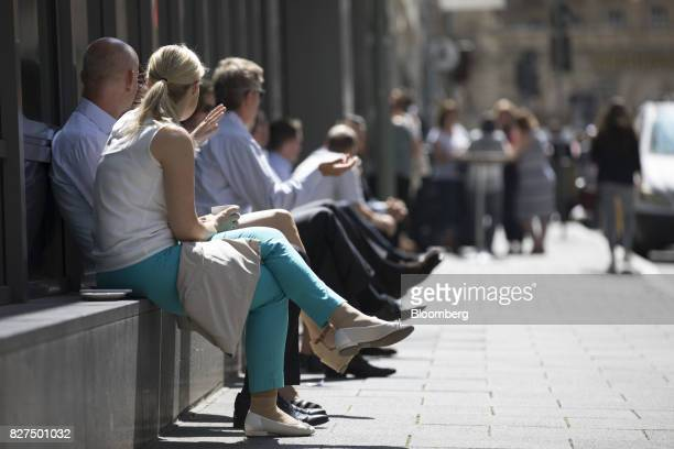 City workers sit in the sunshine during a lunch break in the financial district of Frankfurt Germany on Monday Aug 7 2017 London could lose 10000...