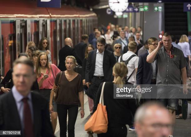 City workers walk on a platform during the morning rush hour commute at Taunusanlage SBahn underground railway station in Frankfurt Germany on Monday...