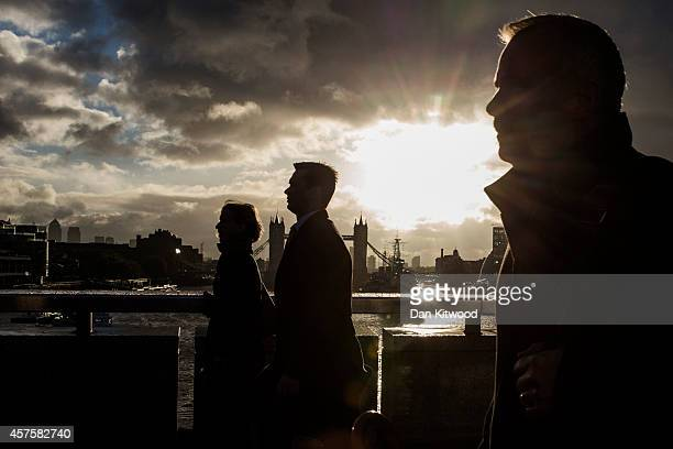 City workers walk over London Bridge as the early morning sun breaks through clouds on October 21 2014 in London England Despite weather warnings...