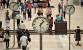 City workers walk past clocks showing 1230 GMT in Canary Wharf east London on August 5 shortly before US employment figures were announced Global...