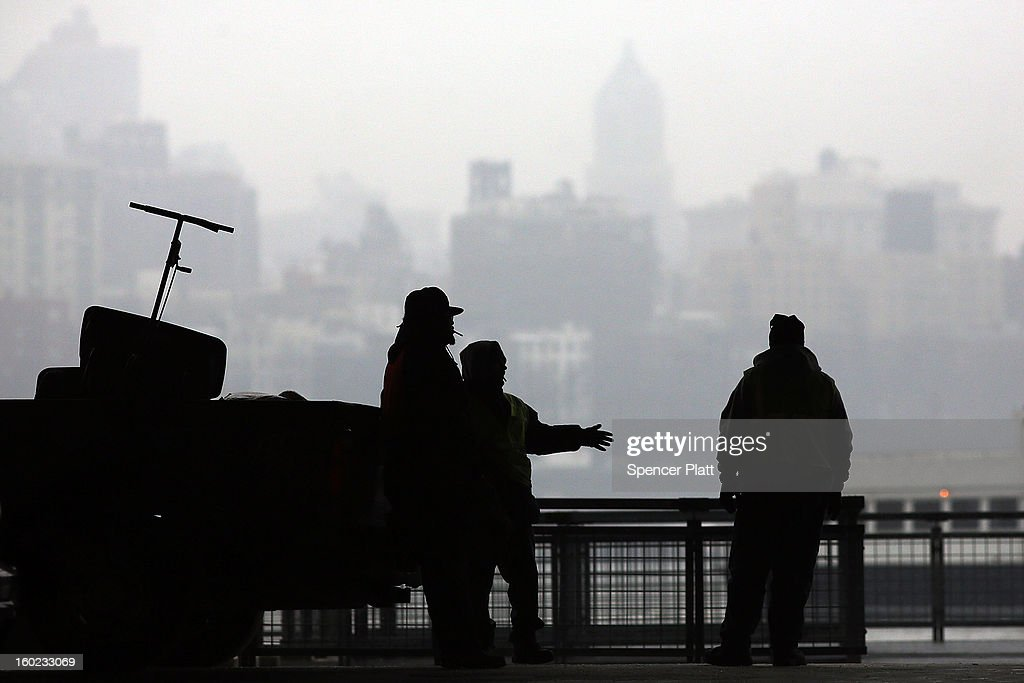 City workers with salt truck take a break from the sleet and snow under a bridge during the morning commute on January 28, 2013 in New York City. Following some of the coldest weather this winter, temperatures are expected to gradually warm during the week in New York.