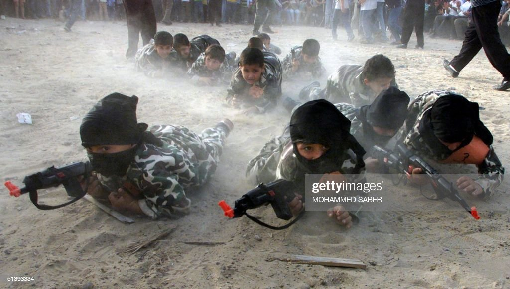 Masked Palestinian children wearing military fatigues and holding toyguns crawl during an anti-US and Israeli rally organised by the Islamic Jihad in Gaza City 31 March 2001. Ten Palestinians, including two little girls and an ambulance man, were wounded by live Israeli army bullets in three separate incidents in the Gaza Strip.