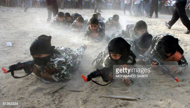 Masked Palestinian children wearing military fatigues and holding toyguns crawl during an antiUS and Israeli rally organised by the Islamic Jihad in...