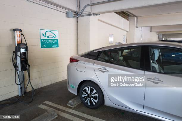 A cityowned plug in hybrid Toyota Prius automobile is plugged in and charging at an electrical vehicle charging station in a municipal garage in...