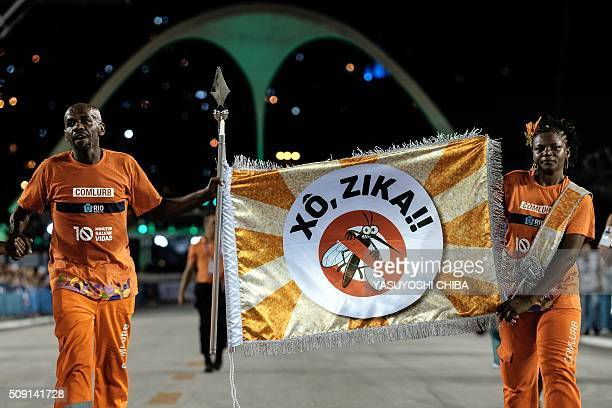 City's cleaning workers carry a flag with that reads 'Out Zika' in portuguese between the samba schools' during the second night of the carnival...