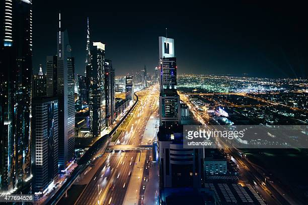 Cityscape at night, multiple lane highway, light streaks, skyscrapers,  Dubai