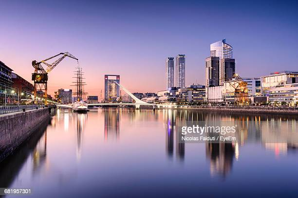 Cityscape By River Against Sky During Sunset