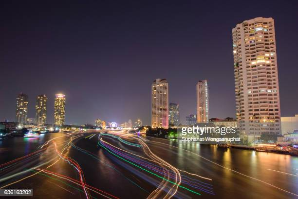 Cityscape of boat light trails on Chao Phraya River in Bangkok, Thailand