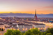 Cityscape of Torino (Turin, Italy) at dusk with colorful moody sky. The Mole Antonelliana towering on the illuminated city below.