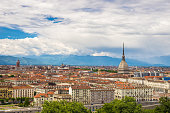 Cityscape of Torino (Turin, Italy) with the Mole Antonelliana towering over the buildings. Wind storm clouds over the Alps in the background.