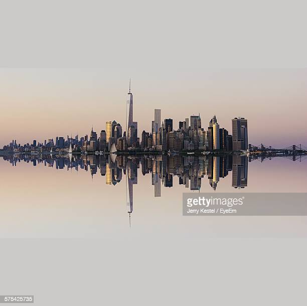 Cityscape Reflecting In River At Dusk