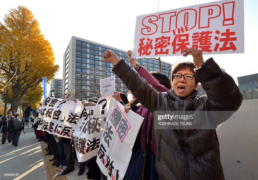 Civic group members raise their fists in the air to protest against a controversial new state secrets bill as they join a human chain surrounding the National Diet in Tokyo on December 4, 2013. The Japanese government is set to pass the controversial bill, which critics say is draconian and will impinge on press freedom and the public's right to know. AFP PHOTO / Yoshikazu TSUNO