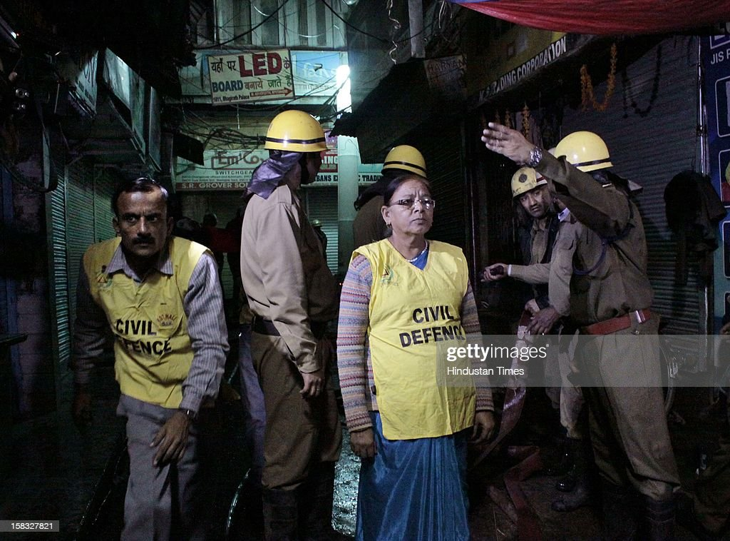 Civil Defence members assist Fire fighters to douse a fire at a godown in Bhagirath Palace, an electrical market of Chandni Chowk area, on December 13, 2012 in New Delhi, India. The blaze erupted at Bhagirath Palace market at around 5.10 pm and 22 fire tenders were immediately rushed to the spot. The fire is doused with no casualties reported.