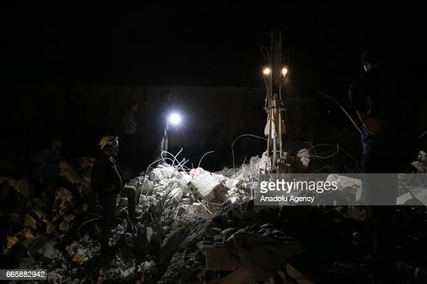 Civil defence staff and citizens nearby launch a search and rescue operation with an excavator after Assad regime bombed the opposition controlled...