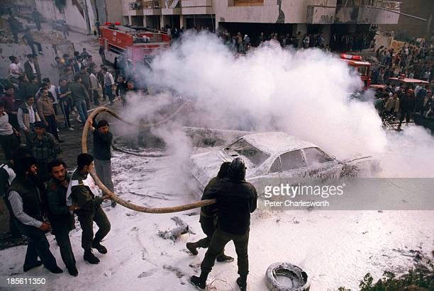 Civil defence volunteers firemen and passersby try to help rescue victims and put out fires caused by a massive car bomb detonated in a main street...