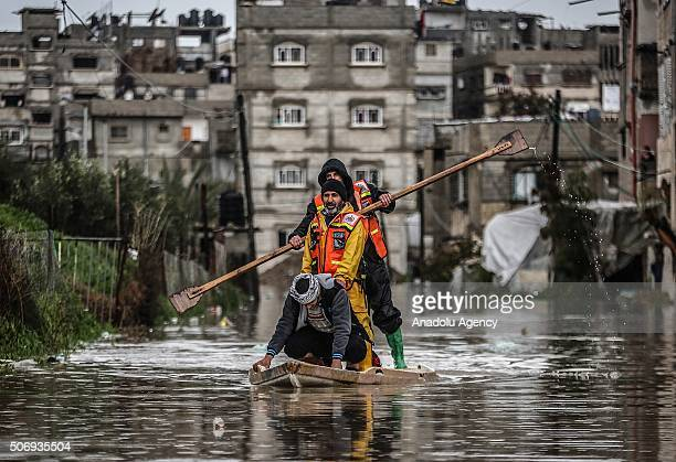 Civil Defence workers use a boat to evacuate people from a flooded area following heavy rainfall in Rafah Gaza on January 26 2016
