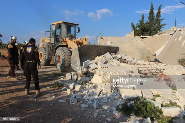 Civil defense members and citizens remove the debris of a building with a construction equipment after Assad regime's airstrikes hit the town of Khan...
