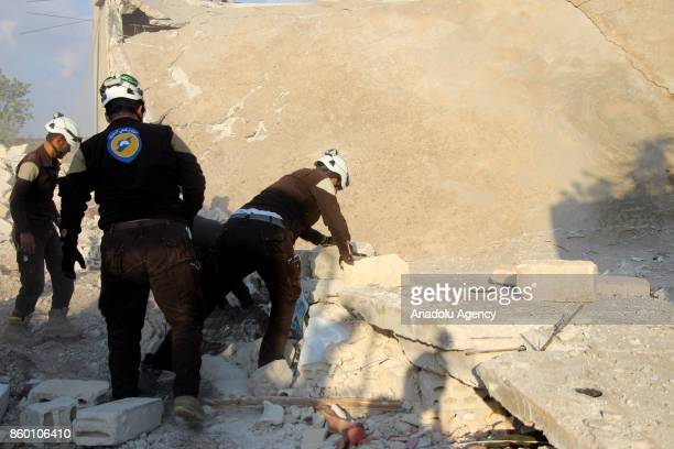 Civil defense members remove the debris of a building after Assad regime's airstrikes hit the town of Khan Shaykhun in Idlib in Syria on October 11...