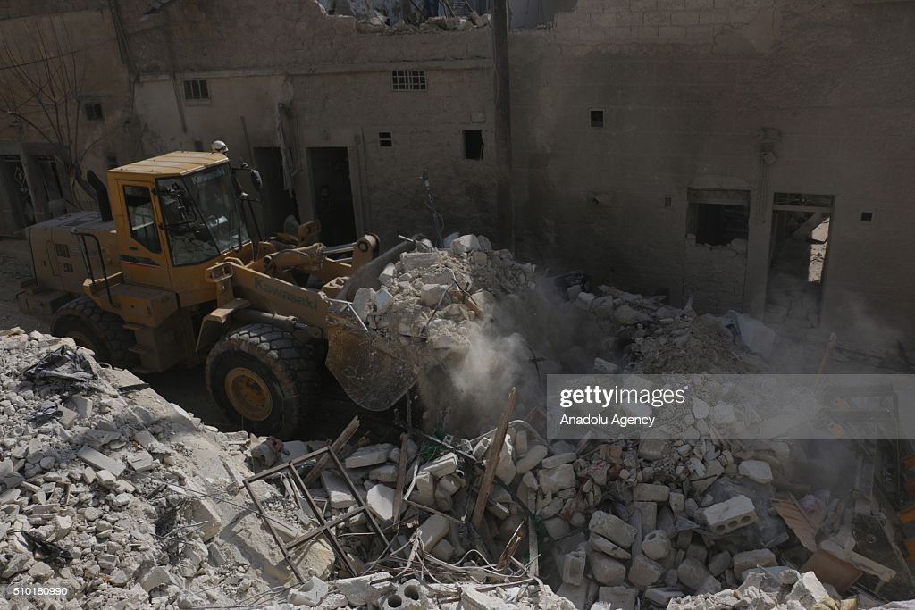 Civil defense members remove the wreckage with a heavy construction equipment after the Russian airstrikes targeted residential areas in opposition controlled Katranci neighborhood of Aleppo, Syria on February 14, 2016.