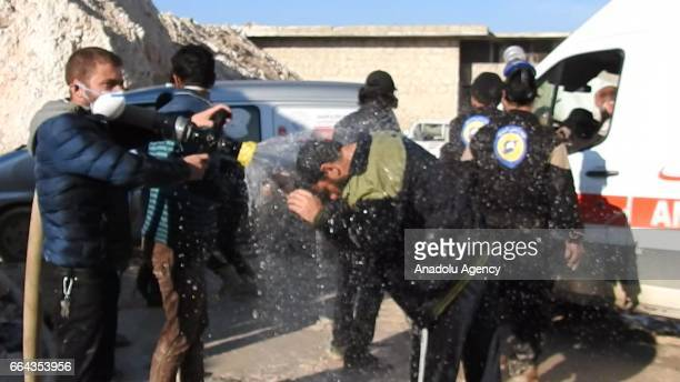 Civil defense members try to reduce the effects of chlorine gas with water as they carry out search and rescue works after a suspected chlorine gas...
