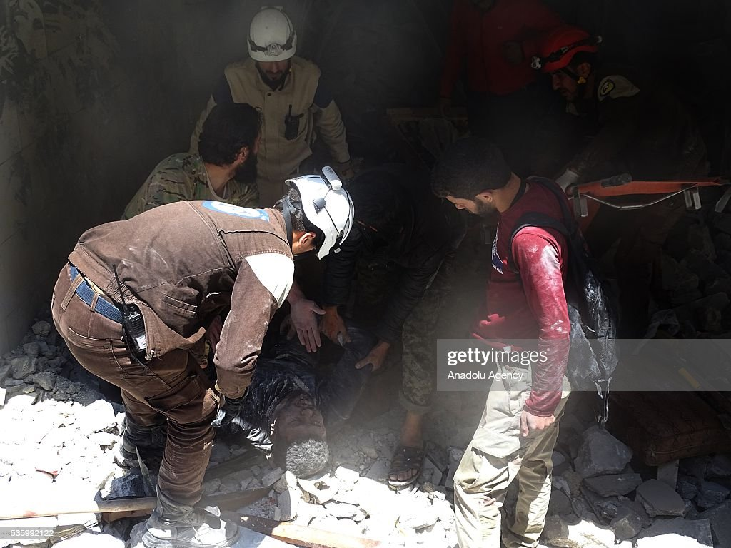 Civil defense members try to rescue a victim from the wreckage of a building after war crafts belonging to Russian Army carried out airstrikes over opposition controlled Kafr Hamrah village of Aleppo, Syria on May 31, 2016.