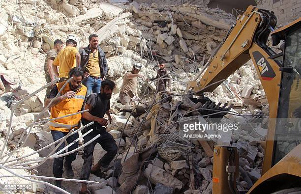 Civil defense members try to rescue people from the wreckage of a field hospital after the Russian airstrikes targeted Sukeri region of Aleppo Syria...