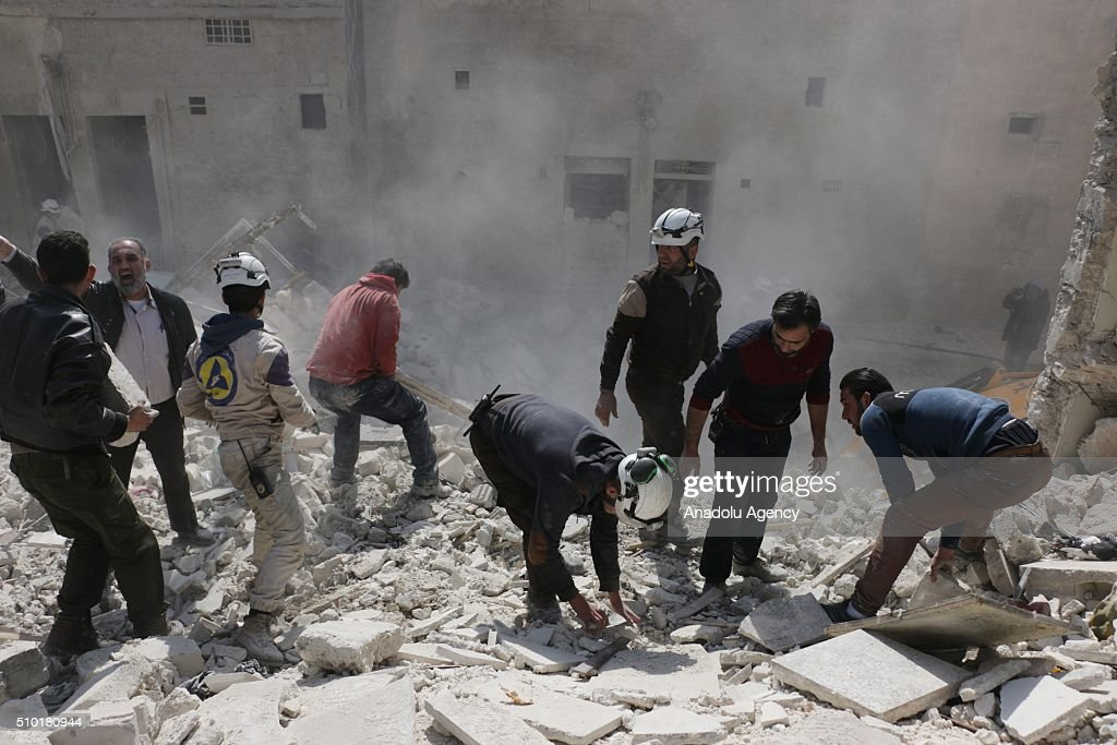 Civil defense members try to rescue victims from the wreckage after the Russian airstrikes targeted residential areas in opposition controlled Katranci neighborhood of Aleppo, Syria on February 14, 2016.