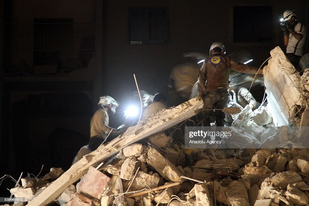 Civil defense members try to rescue victims from the wreckage of National Hospital (Ibn Sina) after the Russian airstrikes targeted Idlib, Syria on May 31, 2016.