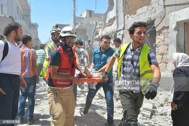 Civil Defense team members carry a wounded woman after Assad regime forces carried out vacuum bomb attack on the Saraqib district of Idlib which is...