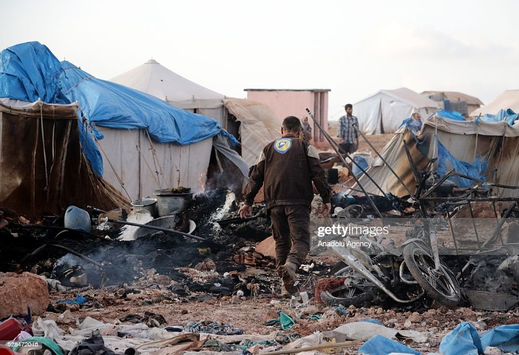 Civil defense team members inspect the damage after a Syrian regime warplane targeted the Kamuna refugee camp near the Syrian town of Sarmada town in the Idlib province after Syrian regime warplane targeted the camp on May 05, 2016. Eight people were killed and another 30 injured when a regime warplane targeted the Kamuna refugee camp.