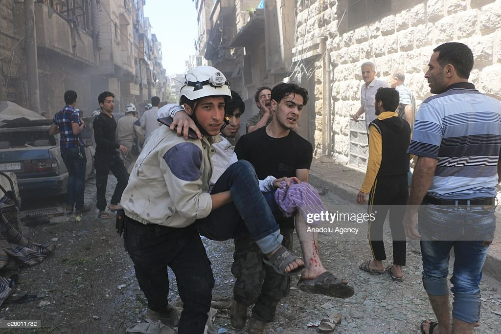 Civil defense workers and civilians carry a wounded man after Assad regime's air strikes on residential areas in Mesekin district of Aleppo in Syria on April 29, 2016.