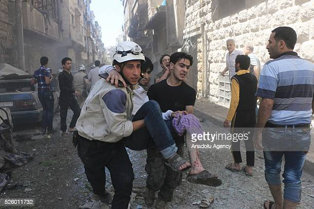 Civil defense workers and civilians carry a wounded man after Assad regime's air strikes on residential areas in Mesekin district of Aleppo in Syria...