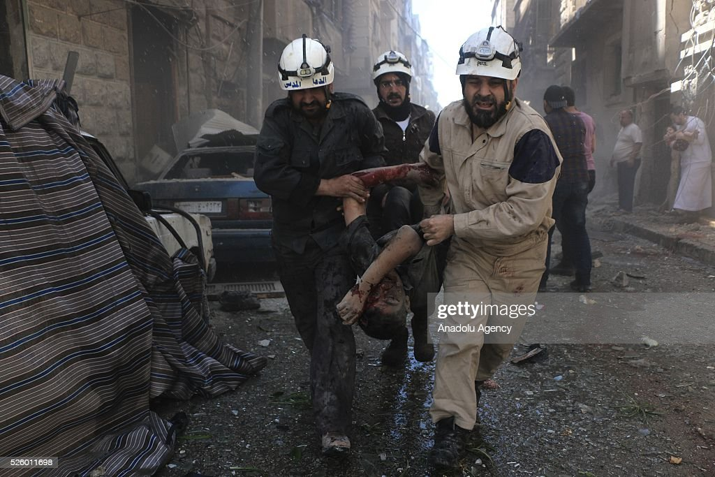 Civil defense workers evacuate dead bodies and woundeds after Assad regime's air strikes on residential areas in Mesekin district of Aleppo in Syria on April 29, 2016.