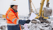 Civil engineer at construction site is inspecting ongoing works according to design drawings in difficult winter conditions