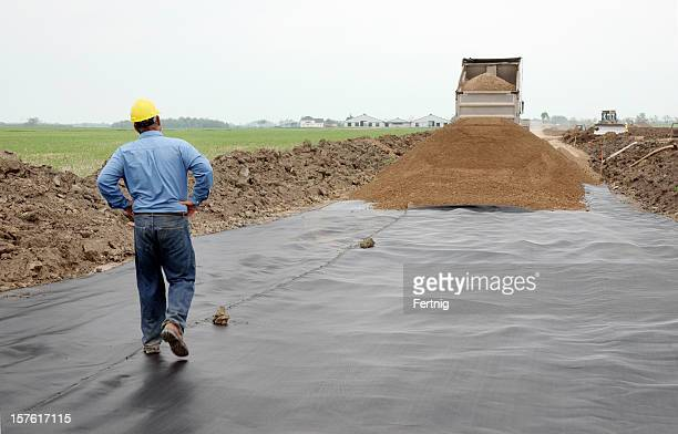 Civil engineer on a road construction site with geo-textile
