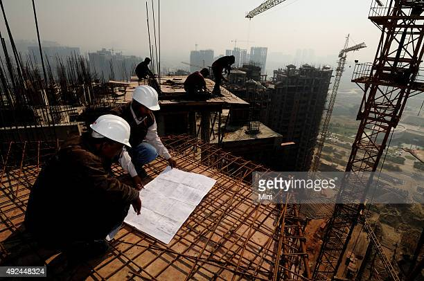 Civil engineers working on edge of under construction high rise building site without any harness on December 21 2012 in Noida India The prospect of...
