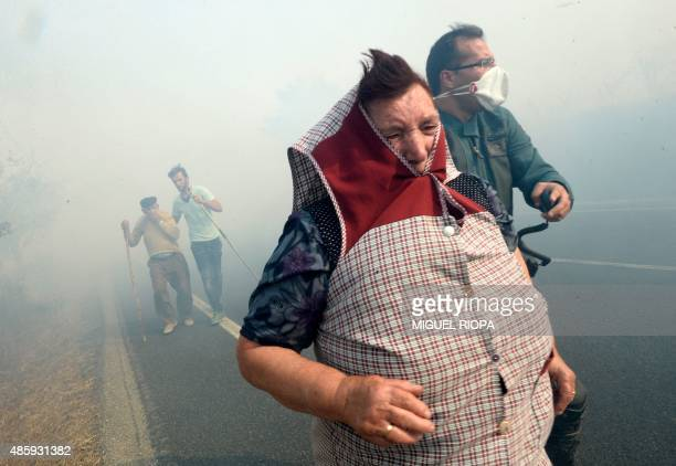 A Civil Guard helps villagers during a fire in the village of Cabreiro some 60 km from Ourense northwestern Spain on August 30 2015 AFP PHOTO/ MIGUEL...