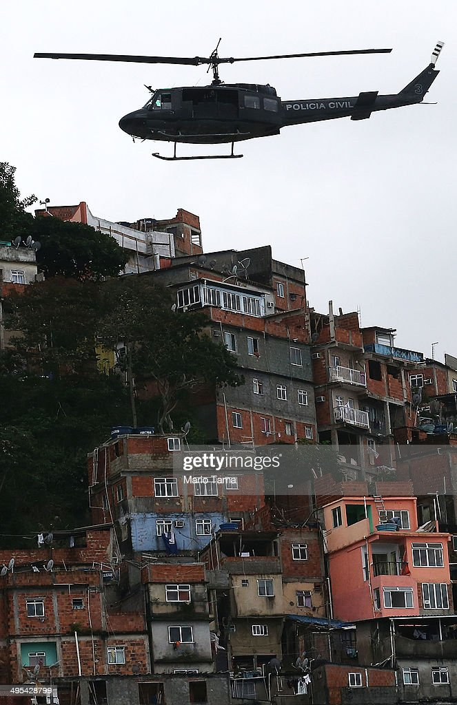 A Civil Police helicopter patrols over the Pavao-Pavaozinho pacified community, or 'favela', on June 3, 2014 in Rio de Janeiro, Brazil. Rio is stepping up security operations ahead of the 2014 FIFA World Cup. Ahead of the World Cup, some of Rio's pacified favelas have seen an increase in violence, including a number of shootings in Pavao-Pavaozinho. Around 10,000 people live in the Cantagalo and Pavao-Pavaozinho communities with a total of around 1.6 million Rio residents residing in shantytowns, many of which are controlled by drug traffickers.