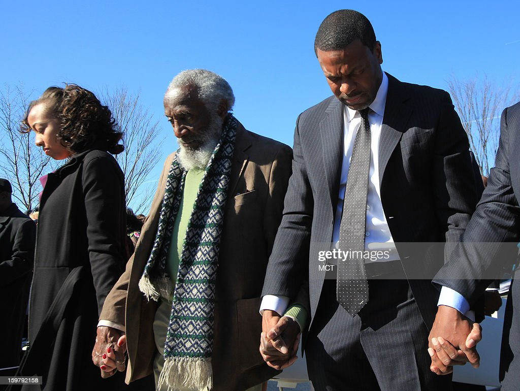 Civil rights activists Dick Gregory, center, and actor Chris Tucker, right, hold hands in solidarity during a wreath laying ceremony at the Martin Luther King Jr. National Monument on Sunday, January 20, 2013 in Washington, D.C. The tribute was made in honor of the Rev. Dr. Martin Luther King Jr., during festivities for the 57th Presidential Inauguration.