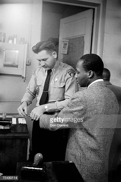 Civil rights leader Martin Luther King Jr being fingerprinted by police after his arrest during the Montgomery bus boycott