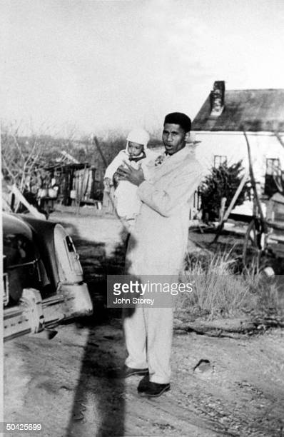 Civil rights leader Medgar Evers holding his baby son Darrell as he stands outside home of a friend ten yrs before he is slain by accused killer...