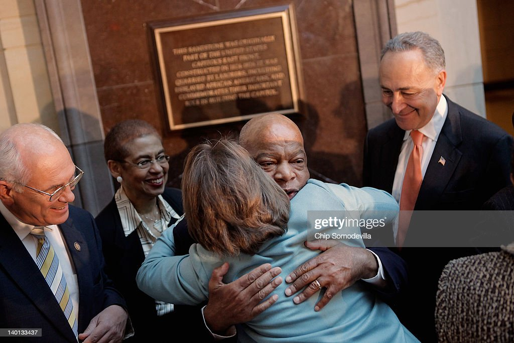 Civil rights pioneer Rep. John Lewis (D-GA) (2nd R) is embraced by former Sen. <a gi-track='captionPersonalityLinkClicked' href=/galleries/search?phrase=Blanche+Lincoln&family=editorial&specificpeople=504930 ng-click='$event.stopPropagation()'>Blanche Lincoln</a> (D-AK) as Sen. <a gi-track='captionPersonalityLinkClicked' href=/galleries/search?phrase=Charles+Schumer&family=editorial&specificpeople=171249 ng-click='$event.stopPropagation()'>Charles Schumer</a> (D-NY) (R), Del. Elenor Holmes Norton (D-DC) and others look on after the unveiling of the new Slave Labor Commemorative Marker in Emancipation Hall at the U.S. Capitol Visitors Center February 28, 2012 in Washington, DC. The marker acknowledges the role that slaves played in the construction of the capitol building, including quarrying the stone for the floors, walls and columns. The stone used for the marker is a block of sandstone that was quarried from Aquia Creek in Virginia and was once part of the East Front portico.